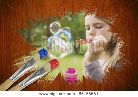 Composite image of little girl blowing bubbles against wooden oak table with paintbrushes poster