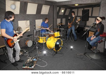 rock band. vocalist girl two musicians with electro guitars and one drummer working in studio.