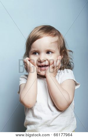 Portrait of a charming baby girl of two she is surprised and holds her head by two hands vertical studio shot poster