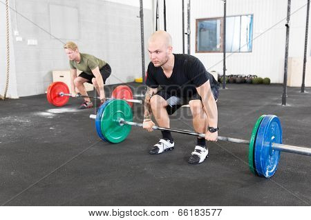 Group trains deadlift at fitness center