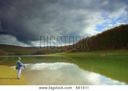 Fisherman Catching Fish On A Lake