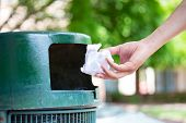 Closeup cropped portrait of someone tossing crumpled piece of paper in trash can isolated outdoors green trees background poster
