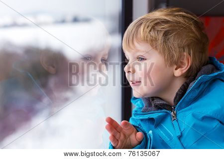 Beautiful Toddler Boy Looking Out Train Window Outside And Traveling