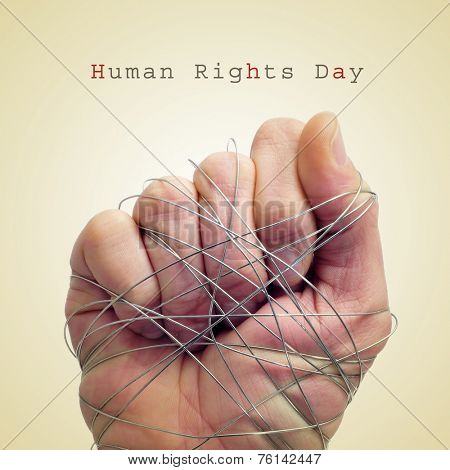 a man hand tied with wire and the text human rights day on a beige background