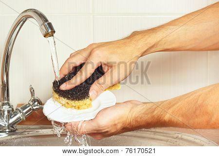 Hands with sponge wash the dirty plate under running water in kitchen