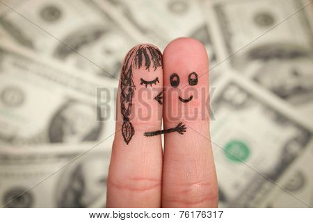 Finger art of a Happy couple. Girl kisses boy on the cheek on the background of money.