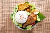 Popular delicious Indonesian local food nasi ayam penyet, indonesian fried chicken rice with sambal belacan. Fresh hot with steam smoke. poster