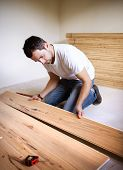 Young handyman installing wooden floor in new house poster