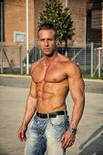 Handsome Muscular Shirtless Hunk Man Outdoor in City Setting. Showing Healthy Body While Looking at Camera poster