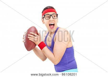 Young nerdy guy in sportswear playing football isolated on white background