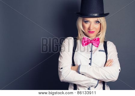 Beautiful Young Woman Wearing Tophat, Bow-tie And Braces Against Grey Background