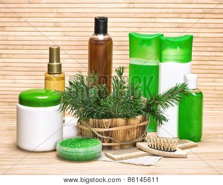 Natural hair care cosmetics and accessories: sea salt shampoo conditioner balm mask oil wooden combs with pine branches on wooden surface poster