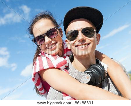 summer holidays and teenage concept - teenagers having fun outside