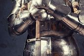 knight wearing armor and standing with two-handed sword poster