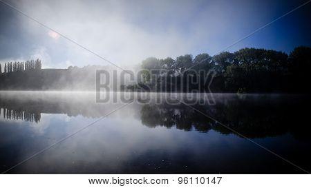 Trees Reflecting On Water Surface On Lake Karapiro In New Zealand. Misty Scenery
