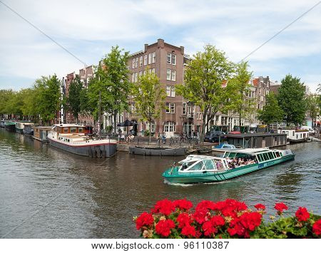 Boat Full Of People Passing A Canal In Amsterdam With Residential Old Buildings Beside It