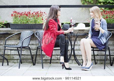 Female Friends Having Conversation In Outdoor Cafe
