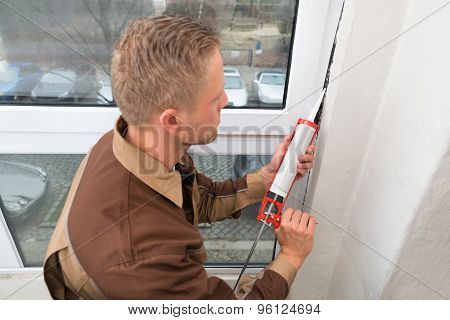 Man In Overall Applying Silicone Sealant