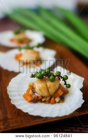 Seared scallops with vegetables on a scallop shell.