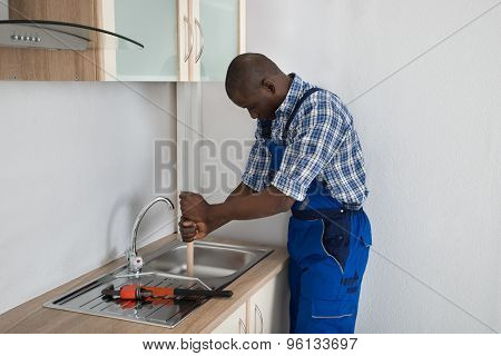 Young Male African Plumber Pressing Plunger In Kitchen Sink poster