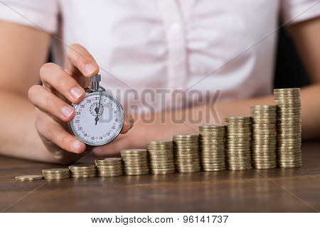 Businessperson With Stopwatch And Stack Of Coins