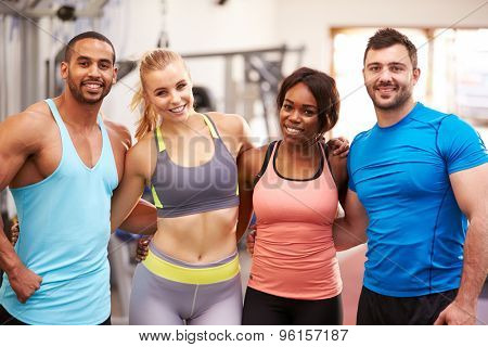 Happy group of gym buddies with arms around each other