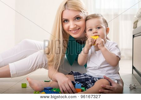 Cheerful young mom is playing with her baby