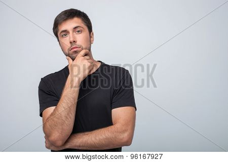 Cheerful young guy is planning to do something