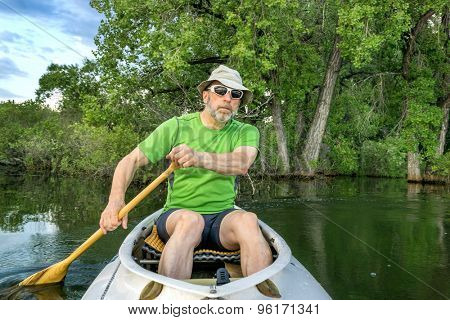 senior male paddler in a decked expedition canoe on a calm lake against background of trees