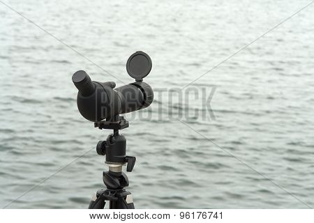 Nature birdwatching spotting scope monocular on a tripod near the water great outdoors activity poster