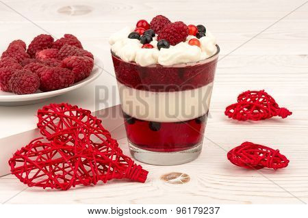 Sweet dessert in glass with cream, jell, raspberries and blueberries on wooden background.