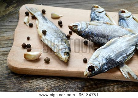 Salty stockfish cod on wooden board with gaarlic and pepper