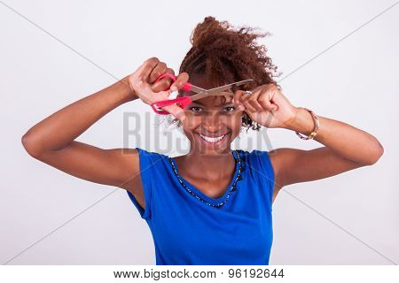 Young African American Woman Cutting Her Frizzy Afro Hair With Scissors - Black People