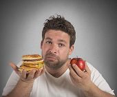 Man undecided between diet and junk food poster