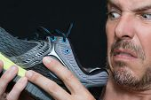 Close-up of a man disgusted by the smell of his running shoe. poster
