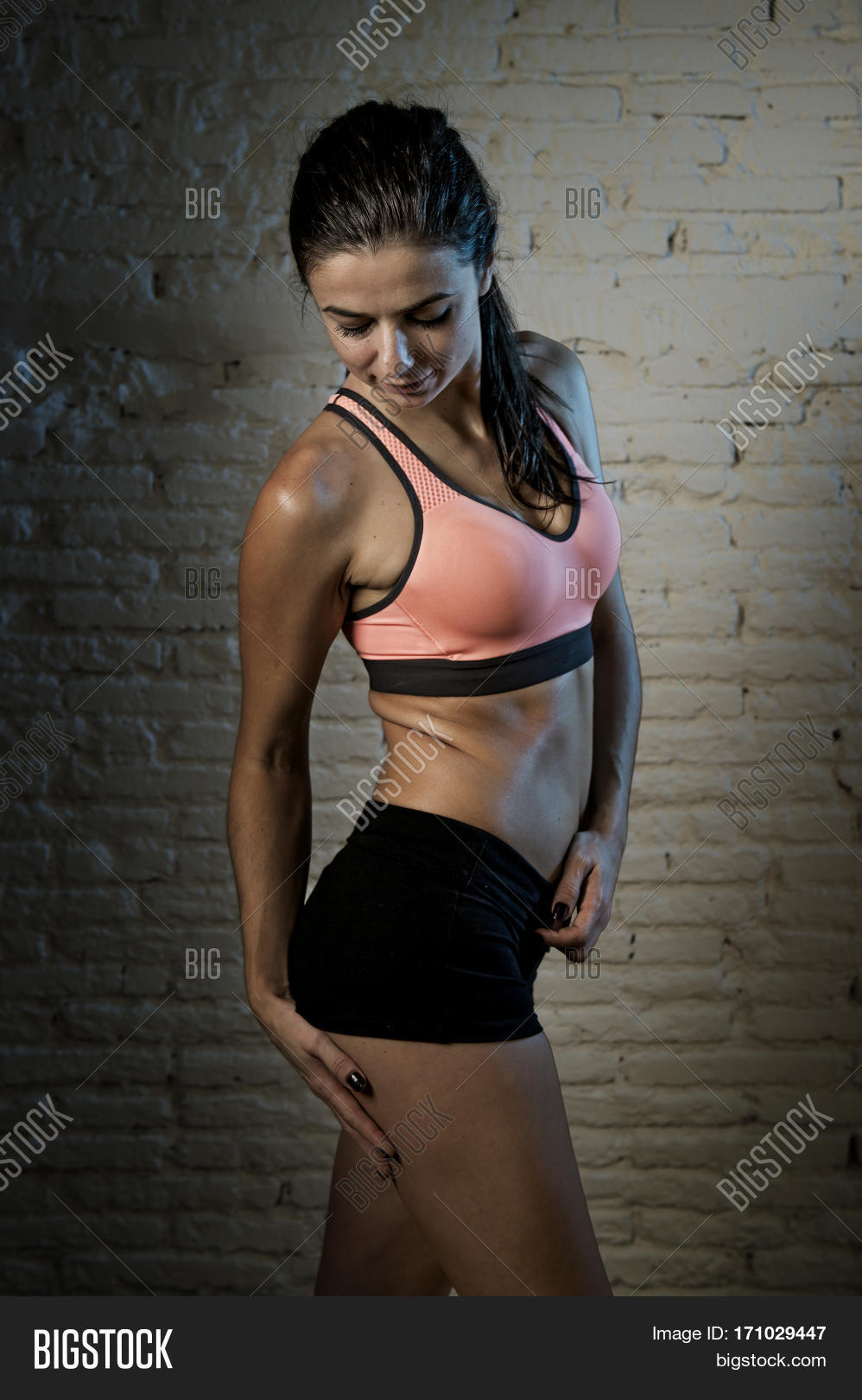 e83a1ce97 young beautiful and sexy woman in fitness top and shorts with perfect  abdomen posing isolated on