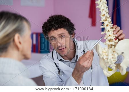 Physiotherapist explaining the spine model to patient in clinic