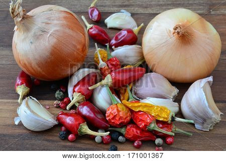Hot spices heap of mixed fresh garlic onion fresh and dry red and yellow chilli peppers and red black and white peppercorns on dark wooden background