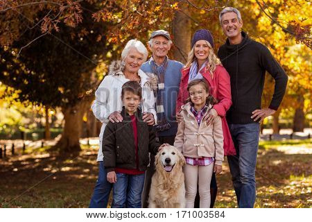 Portrait of smiling multi-generation family standing with dog at park during autumn