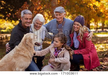 Happy multi-generation family with dog at park during autumn