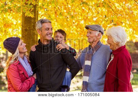 Happy multi-generation family standing at park during autumn