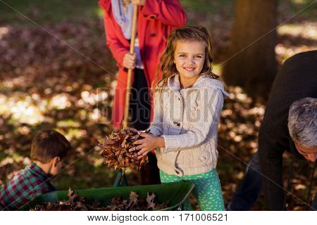 Girl picking up autumn leaves with family at park