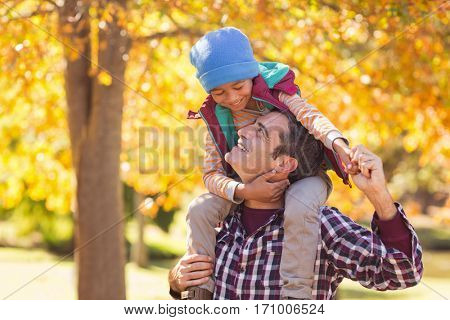Cheerful father carrying son on shoulder at park during autumn