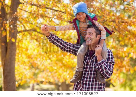 Cheerful father carrying son on shoulder against autumn tree at park