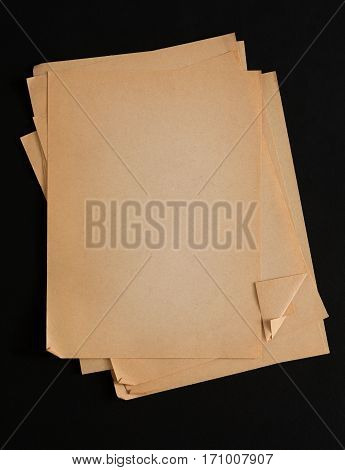 old paper isolated on black background. Aged craft obsolete sheets pile with copy space