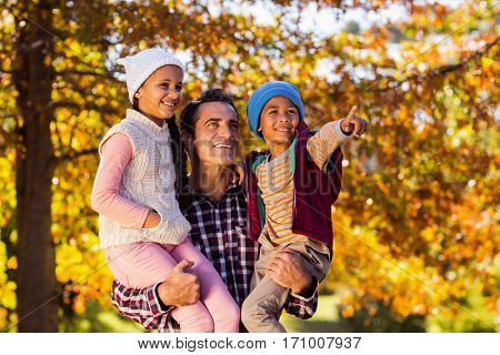 Happy father looking away while carrying children at park during autumn