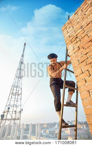 Handsome builder with bare torso in hat climb on ladder up and looking down. Ladder leaning on brick wall at un finished building. High TV tower on background.