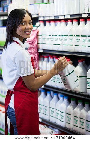 Portrait of female staff arranging milk bottle in shelf at dairy section of supermarket