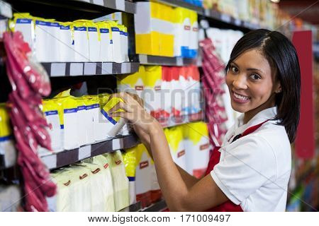 Portrait of smiling female staff arranging goods in grocery section of supermarket