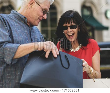 Man surprising woman with gift paper bag